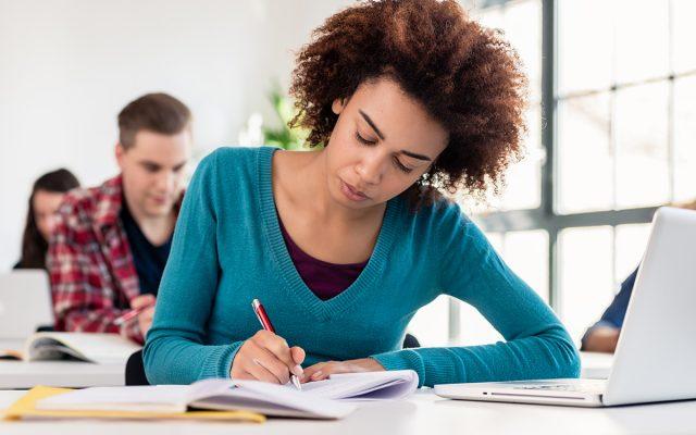 Opiskelija keskittyy kirjoittamiseen