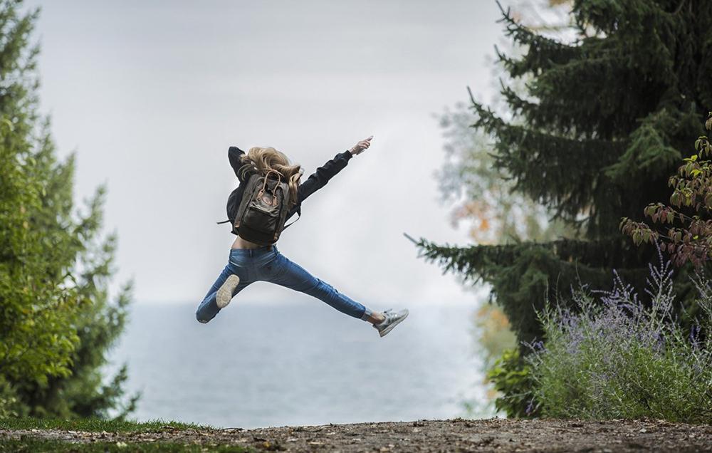 takaa otettu kuva tytöstä, on hypännyt ilmaan polulla