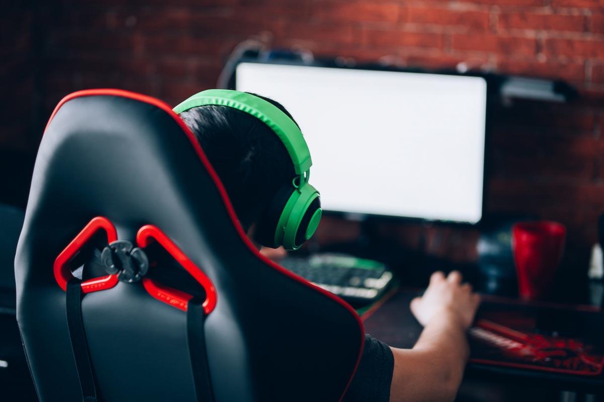 pelaaja istuu tuolissa ja pelaa tietokoneella